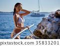 redhair woman in bikini relaxed on quiet sea with warm sunset co 35833201