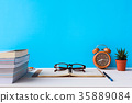 Books and glasses on a white wooden table  35889084