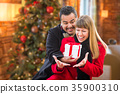 Mixed Race Couple Sharing Christmas In Front of Decorated Tree. 35900310