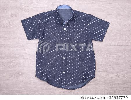 blue polka dot shirt for boys on wood background. 35957779