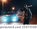 Maniac with bloody baseball bat against black car 35973598