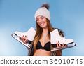 Woman holding ice skates, winter sport 36010745