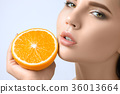 Beautiful woman's face with juicy orange 36013664