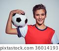 smiling teen boy in sportswear holding soccer ball 36014193