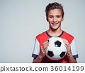 smiling teen boy in sportswear holding soccer ball 36014199