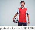 smiling teen boy in sportswear holding soccer ball 36014202