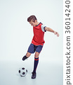photo young teen boy with soccer ball doing flying kick 36014240