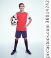 Photo of teen boy in sportswear holding soccer ball 36014242