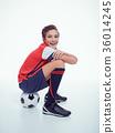 smiling teen boy in sportswear holding soccer ball 36014245