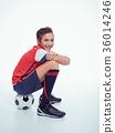 smiling teen boy in sportswear holding soccer ball 36014246