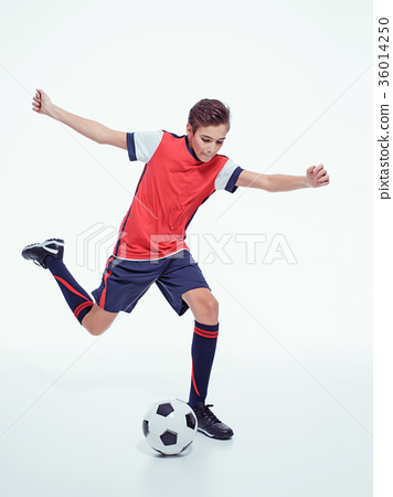 photo young teen boy with soccer ball doing flying kick 36014250