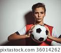 Photo of teen boy in sportswear holding soccer ball 36014262