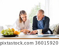 Health visitor and a senior man with tablet during 36015920