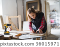 Young woman worker in the carpenter workroom. 36015971