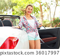Woman is standing near car with the keys in hand 36017997
