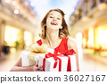 Young woman holding a stack of gift boxes 36027167