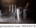 Photo of two wineglasses, iron bucket with bottle 36039578