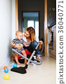 Young mother with a baby boy doing housework. 36040771