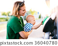 Young mother with baby boy at the petrol station. 36040780