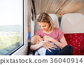 Young mother travelling with baby by train. 36040914