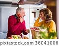 Senior couple preparing food in the kitchen. 36041006