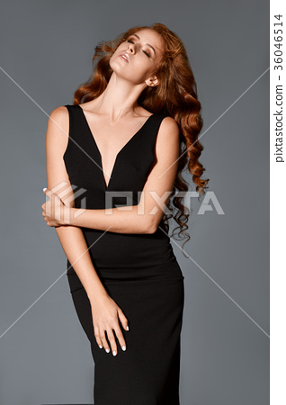 Attractive slim ginger woman in black dress with wave hairstyle curly in studio 36046514