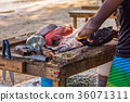Fisher's hands cleaning fish on wooden table 36071311