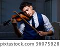 Young musician man practicing playing violin at 36075928