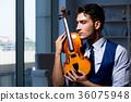 Young musician man practicing playing violin at 36075948