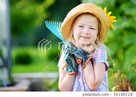 Adorable little girl wearing straw hat holding garden tools 36106228