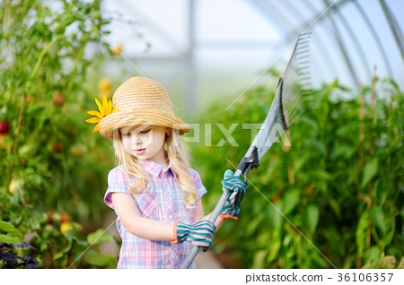 Adorable little girl wearing straw hat holding garden tools 36106357