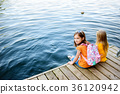 Two cute little girls sitting on a wooden platform by the river or lake 36120942