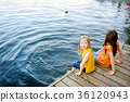 Two cute little girls sitting on a wooden platform by the river or lake 36120943