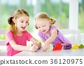 Two cute little sisters having fun together with colorful modeling clay at a daycare 36120975