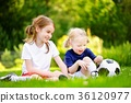 Two cute little sisters having fun playing a soccer game 36120977