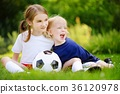 Two cute little sisters having fun playing a soccer game 36120978