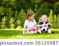 Two cute little sisters having fun playing a soccer game on sunny summer day 36120987