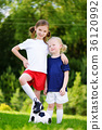 Two cute little sisters having fun playing a soccer game on sunny summer day 36120992