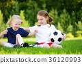Two cute little sisters having fun playing a soccer game on sunny summer day 36120993