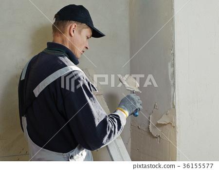 Man gets manually gypsum plaster 36155577