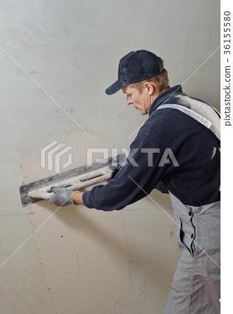 Man gets manually gypsum plaster 36155580