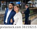 couple waiting on platform at train station 36159215