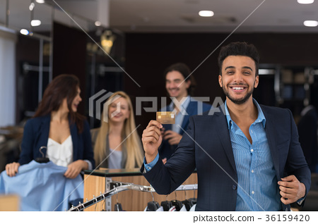 Happy Smiling Man With Credit Card In Clothes Shop 36159420