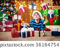 Boy lying on the floor with presents near 36164754