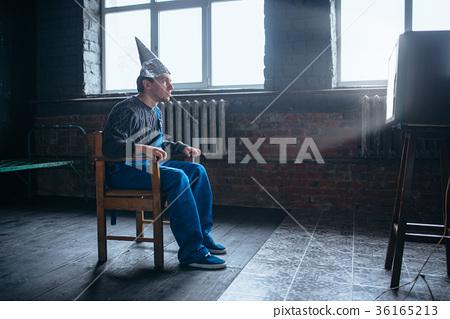 Afraided man in aluminum foil helmet sits in chair 36165213