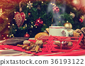Cup of hot tea on with behind christmas tree. 36193122