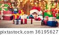 Boy lying on the floor with presents near 36195627
