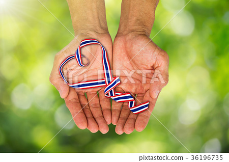 Hands holding heart shaped Thai color ribbon 36196735