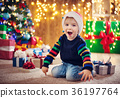 Boy and sitting on the floor with presents near 36197764