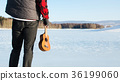 Man with ukulele on a frozen lake 36199060